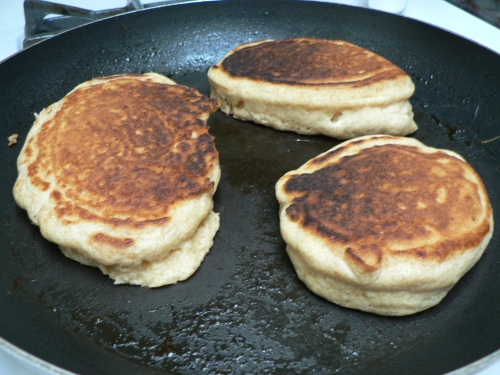 Three grain pancakes, puffing up in the pan.